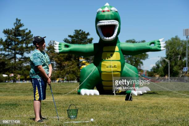 Leo Bulikh listens to instruction before hitting a bucket of golf balls at an inflatable dinosaur at Del Mar Park on June 14 in Aurora Colorado Free...