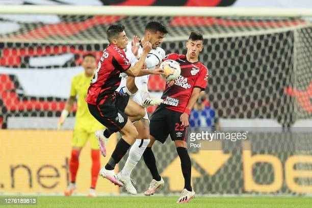 Leo Cittadini and Pedrinho viwe for the ball with Felipe Campos of ColoColo during a group C match of Copa CONMEBOL Libertadores 2020 between...