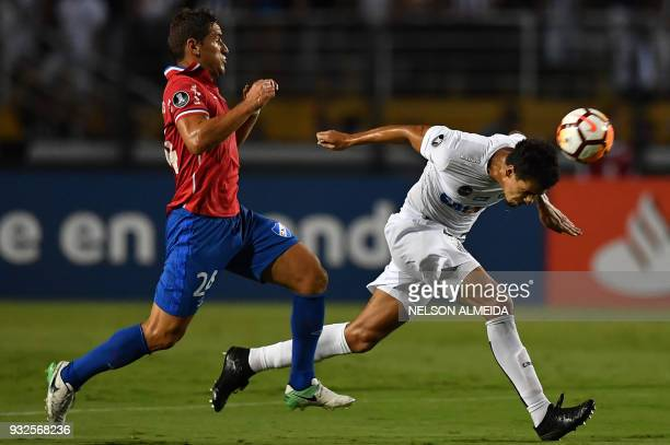 Leo Cittadini of Brazil's Santos vies for the ball with Gonzalo Bergessio of Uruguay's Nacional during their 2018 Copa Libertadores football match...