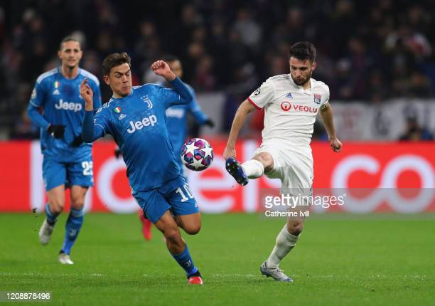 Leo Dubois of Olympique Lyon is challenged by Paulo Dybala of Juventus during the UEFA Champions League round of 16 first leg match between Olympique...