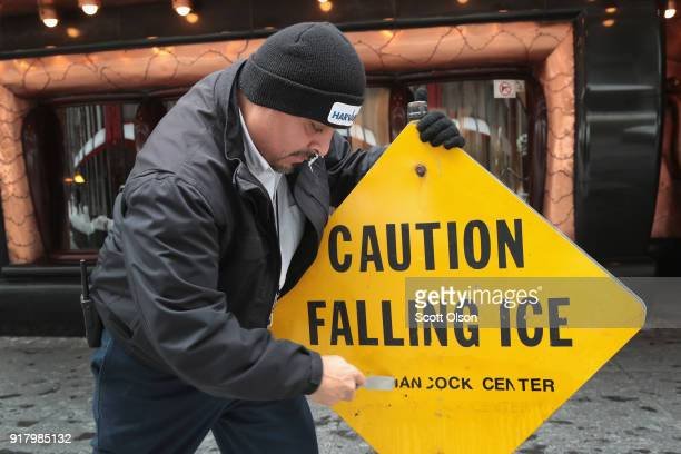 Leo Jacquez removes the John Hancock name fom a sign outside of the John Hancock Center one of Chicago's most famous skyscrapers on February 13 2018...
