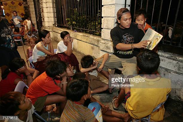 Leo James Portales a volunteer and social worker with Childhope Asia reads a book to street children during a twice weekly session to try and help...