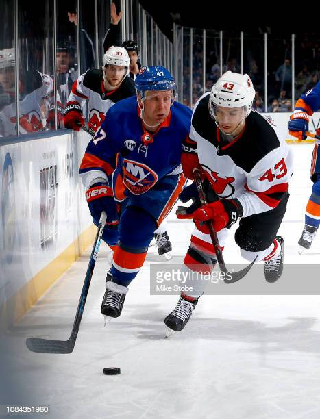 Leo Komarov of the New York Islanders and Brett Seney of the New Jersey Devils chase down the puck during the third period at Nassau Veterans...