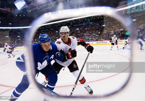 Leo Komarov of the Toronto Maple Leafs and Erik Burgdoerfer of the Ottawa Senators chase the puck during the second period at the Air Canada Centre...