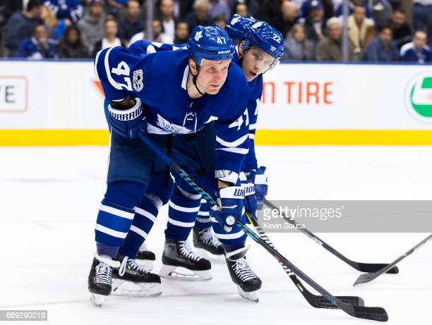 Leo Komarov of the Toronto Maple Leafs and Nikita Zaitsev get set for a faceoff against the Calgary Flames during the third period at the Air Canada...
