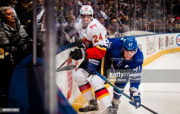 Leo Komarov of the Toronto Maple Leafs battles with Travis Hamonic of the Calgary Flames during the first period at the Air Canada Centre on December...