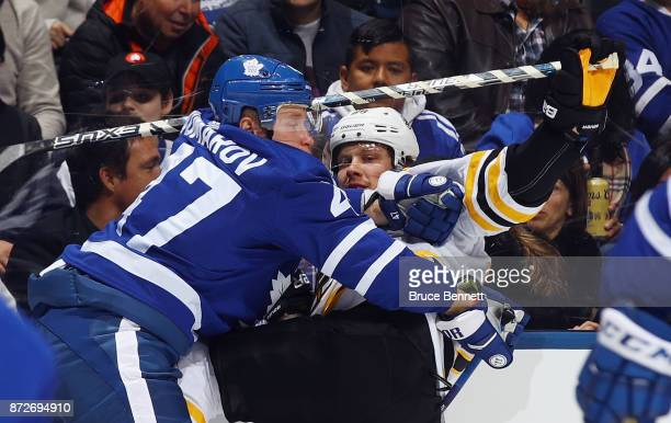 Leo Komarov of the Toronto Maple Leafs hits David Pastrnak of the Boston Bruins during the third period at the Air Canada Centre on November 10 2017...