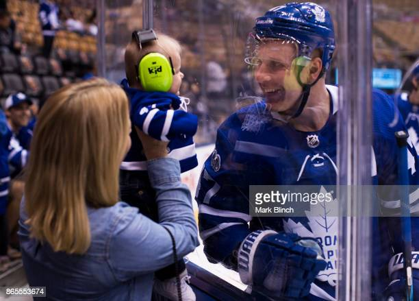 Leo Komarov of the Toronto Maple Leafs looks at his child through the glass during warm up before facing the Los Angeles Kings at the Air Canada...