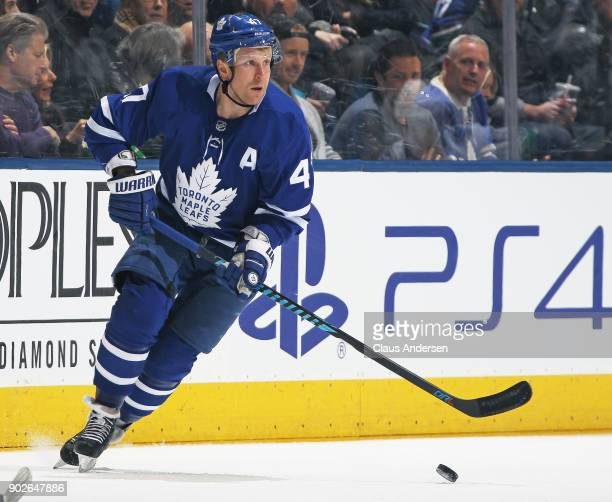 Leo Komarov of the Toronto Maple Leafs skates with the puck against the Vancouver Canucks during an NHL game at the Air Canada Centre on January 6...