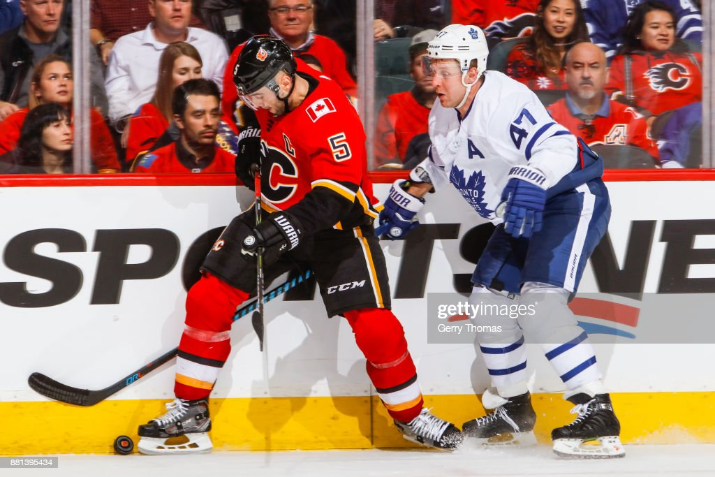 Leo Komarov #47 of the Toronto Maple Leafs tries to steal the puck from Mark Giordano #5 of the Calgary Flames in an NHL game against the Toronto Maple Leafs at the Scotiabank Saddledome on November 28, 2017 in Calgary, Alberta, Canada.