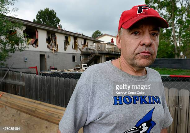 Leo Lech stands on a pile of wood in his neighbors yard that overlooks the back of his home A fence was place around the perimeter of his home after...