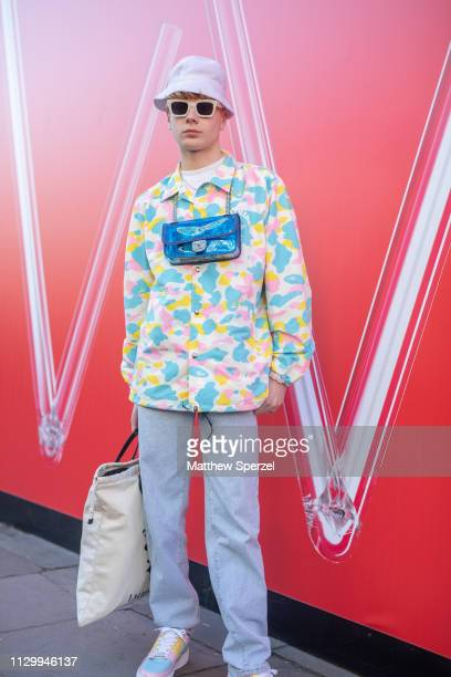 Leo Mandella is seen on the street wearing pastel camo shirt bucket hat sunglasses and Gucci blue bag with tote bag during London Fashion Week...