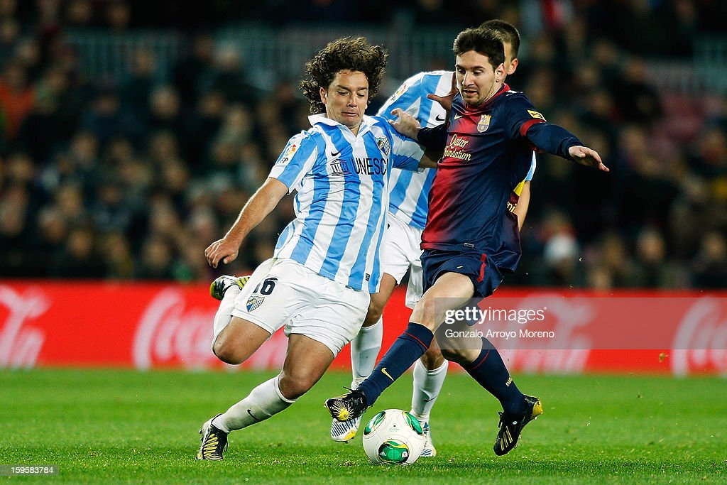 Leo Messi (R) of Barcelona FC competes for the ball with Manuel Ronaldo Iturra (L) of Malaga CF during the Copa del Rey Quarter Final match between Barcelona FC and Malaga CF at Camp Nou on January 16, 2013 in Barcelona, Spain.