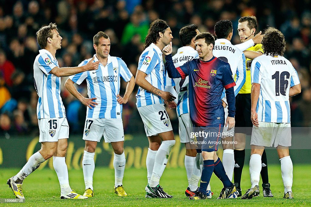 Leo Messi of Barcelona FC passes through Malaga CF players after the referee Mr. Rubio Palomino (2ndR) has shown a red card to Sergio Sanchez (3dL) of Malaga CF during the Copa del Rey Quarter Final match between Barcelona FC and Malaga CF at Camp Nou on January 16, 2013 in Barcelona, Spain.