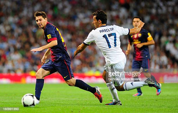Leo Messi of FC Barcelona duels for the ball with Alvaro Arbeloa of Real Madrid during the Supercopa second leg match between Real Madrid and...