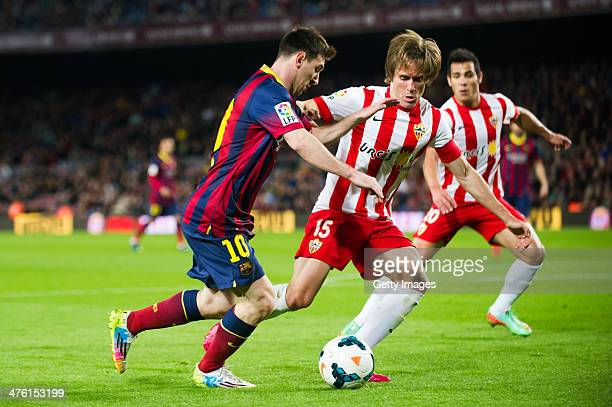 Leo Messi of FC Barcelona duels for the ball with Miguel Angel Garcia 'Corona' of UD Almeria during the La Liga match between FC Barcelona and UD...
