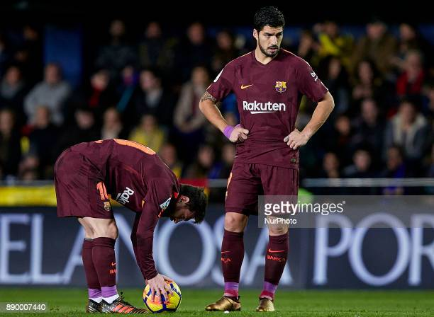 Leo Messi of FC Barcelona puts the ball on the pitch next to his teammate Luis Suarez during the La Liga game between Villarreal CF and FC Barcelona...