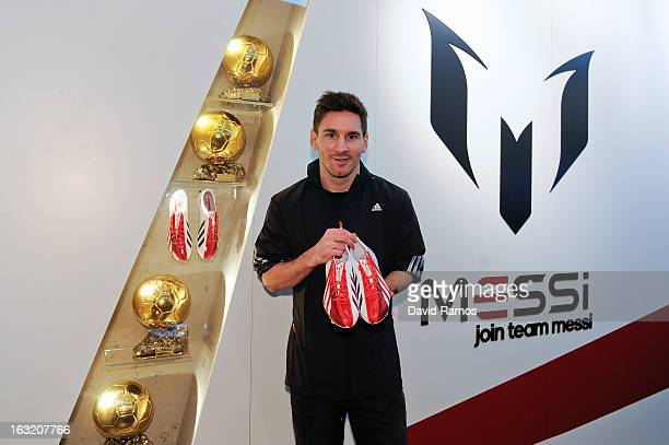 Leo Messi with his four successive FIFA Ballon d'Or trophies and holding the adizero f50 Messi boots during his visit to the new adidas Messi Gallery...