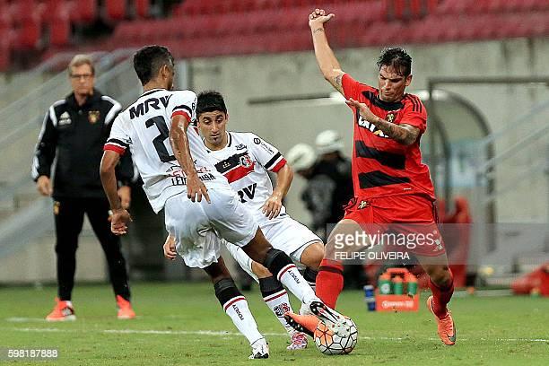 Leo Moura of Brazilian Santa Cruz vies for the ball with Mark Gonzalez of Brazilian Sport Recife during a Sudamericana Cup football match in Recife...