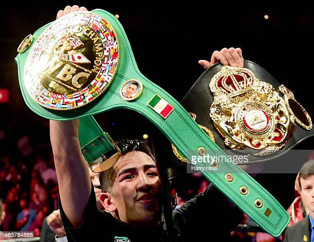 Leo Santa Cruz holds up his two belts after beating Abner Mares of Mexico in a 12 round decision during the WBC diamond featherweight and WBA...