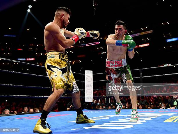 Leo Santa Cruz reaches to punch Abner Mares of Mexico during the first round of the WBC diamond featherweight and WBA featherweight championship bout...
