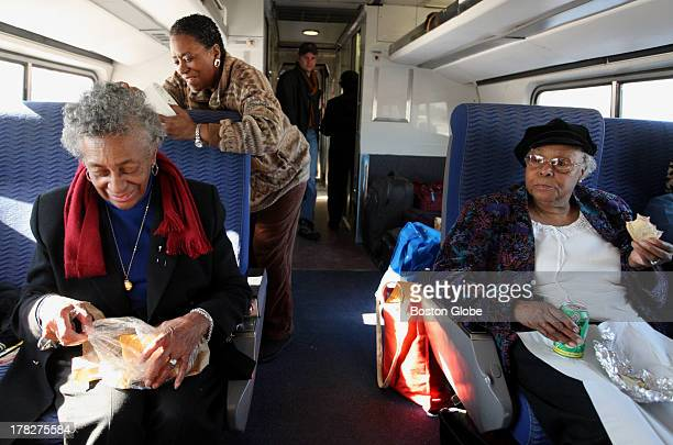 Leola Wilson left serves up coconut bread as Charlotte Nelson standing and Lillian F Moore right settle in on train on their journey to Washington DC...