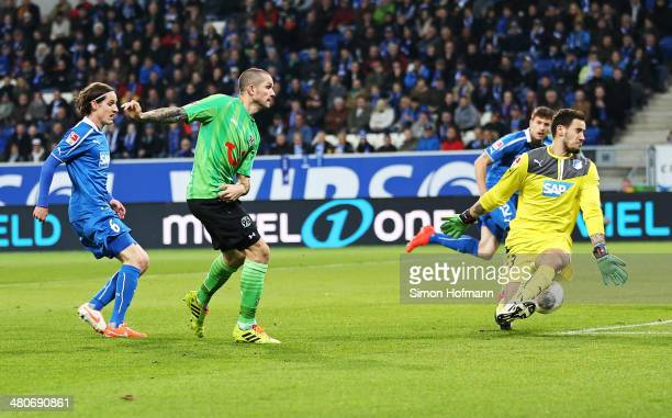 Leon Andreasen of Hannover scores his team's first goal against goalkeeper Jens Grahl of Hoffenheim during the Bundesliga match between 1899...