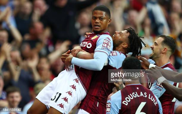 Leon Bailey of Aston Villa is congratulated by Tyrone Mings and teammates after his corner-kick led to their team's second goal, an own goal scored...