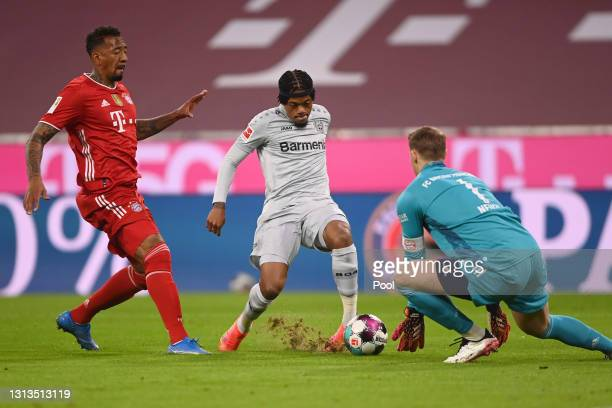 Leon Bailey of Bayer Leverkusen takes a shot under pressure from Jerome Boateng and Manuel Neuer of FC Bayern Muenchen during the Bundesliga match...