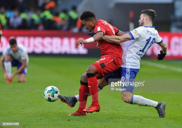 Leon Bailey of Leverkusen and Daniel Caligiuri of Schalke battle for the ball during the Bundesliga match between Bayer 04 Leverkusen and FC Schalke...