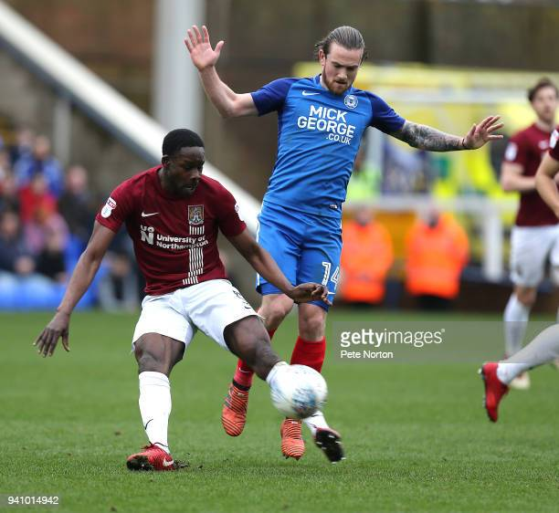 Leon Barnett of Northampton Town attempts to clear the ball under pressure from Jack Marriott of Peterborough United during the Sky Bet League One...