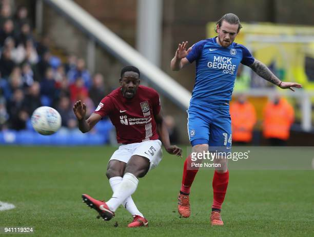 Leon Barnett of Northampton Town clears the ball under pressure from Jack Marriott of Peterborough United during the Sky Bet League One match between...