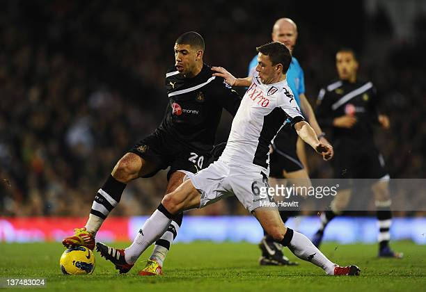 Leon Best of Newcastle United is challenged by Chris Baird of Fulham during the Barclays Premier League match between Fulham and Newcastle United at...