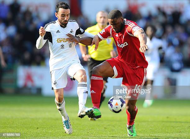 Leon Britton of Swansea City and Victor Anichebe of West Bromwich Albion in action during the Barclays Premier League match between Swansea City and...