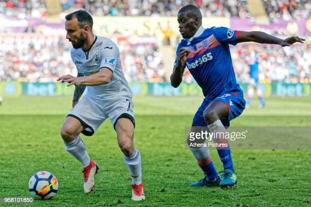 Leon Britton of Swansea City closely marked by Badou Ndiaye of Stoke City during the Premier League match between Swansea City and Stoke City at The...