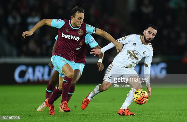 Leon Britton of Swansea City is challenged by Mark Noble during the Barclays Premier League match between Swansea City and West Ham United at the...
