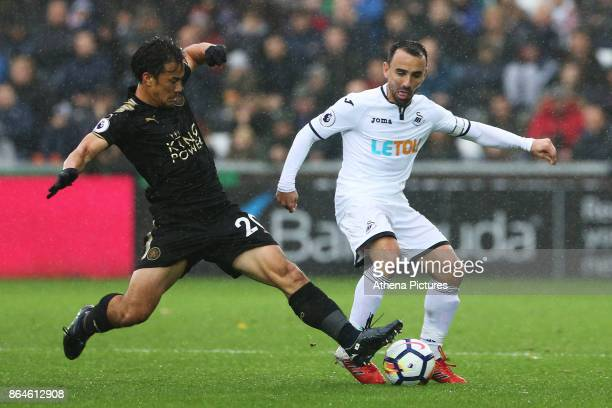 Leon Britton of Swansea City is challenged by Shinji Okazaki of Leicester City during the Premier League match between Swansea City and Leicester...