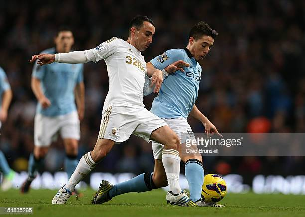 Leon Britton of Swansea City tangles with Samir Nasri of Manchester City during the Barclays Premier League match between Manchester City and Swansea...