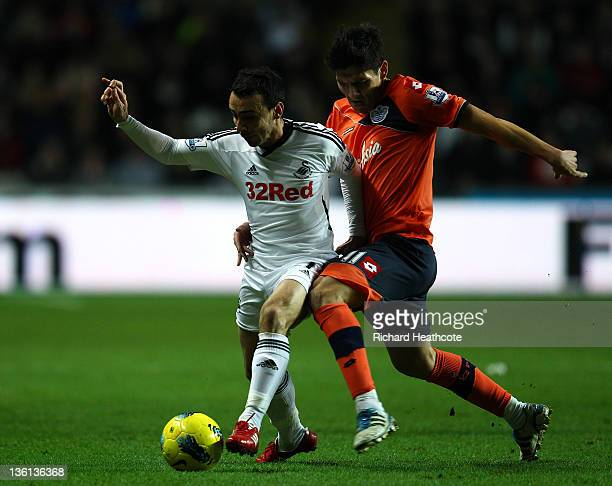 Leon Britton of Swansea holds off Alejandro Faurlín of QPR during the Barclays Premier League match between Swansea City and Queens Park Rangers at...