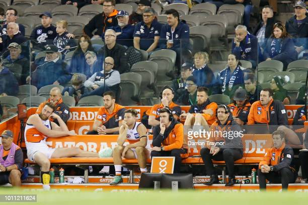 Leon Cameron Senior Coach of the Giants sits on the interchange bench with injured players Dawson Simpson Toby Greene and Brent Deledio during the...