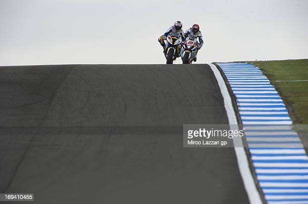 Leon Camier of Great Britain and Crescent Fixi Suzuki and Marco Melandri of Italy and BMW Motorrad GoldBet SBK head down a straight during the World...