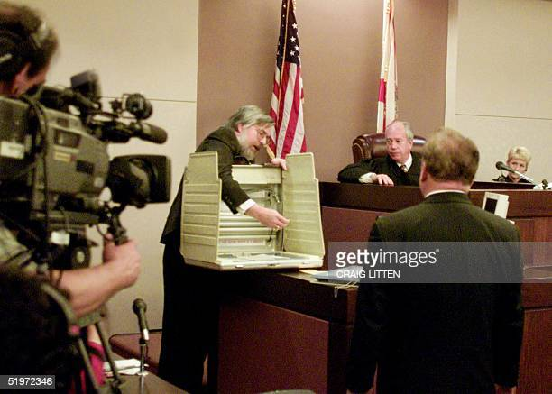 Leon County Circuit Court Judge N Sanders Sauls listens as witness Kendall Brace demonstrates a voting box 02 December 2000 in Tallahassee Florida at...