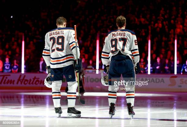 Leon Draisaitl and Connor McDavid of the Edmonton Oilers listen to the national anthem during their NHL game against the Vancouver Canucks at Rogers...
