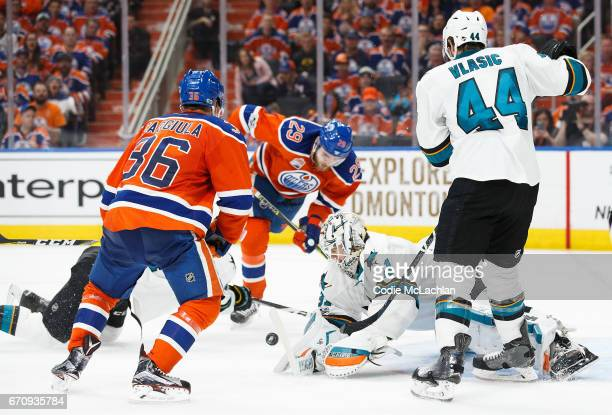Leon Draisaitl and Drake Caggiula of the Edmonton Oilers try to get a shot on goalie Martin Jones of the San Jose Sharks in Game Five of the Western...