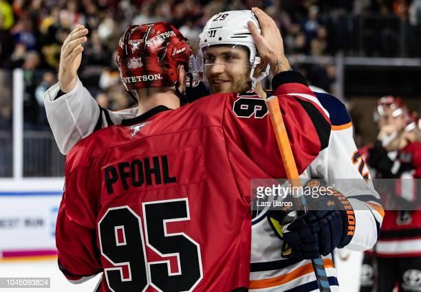 Leon Draisaitl of Edmonton hughs Fabio Pfohl of Haie after the NHL Global Series Challenge game between Edmonton Oilers and Kolner Haie at Lanxess...
