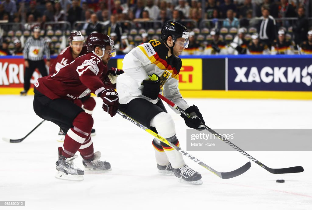 Leon Draisaitl of Germany is challenged by Teodors Blugers of Latvia during the Germany v Latvia match of the 2017 IIHF Ice Hockey World Championships at Lanxess Arena on May 16, 2017 in Cologne, Germany.