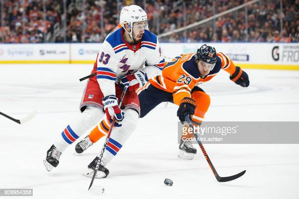 Leon Draisaitl of the Edmonton Oilers battles against Mika Zibanejad of the New York Rangers at Rogers Place on March 3 2018 in Edmonton Canada