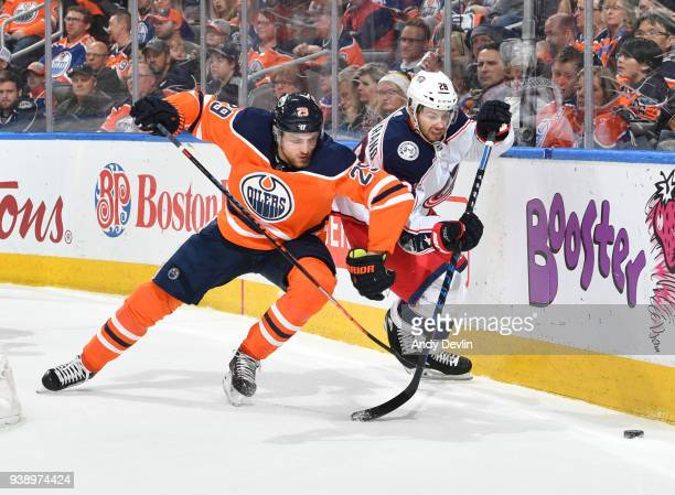 Leon Draisaitl of the Edmonton Oilers battles for the puck against Oliver Bjorkstrand of the Columbus Blue Jackets on March 27 2018 at Rogers Place...