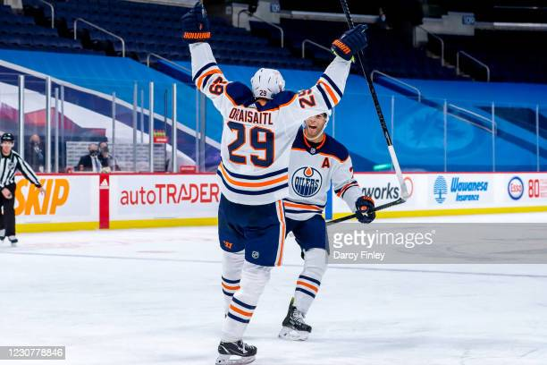 Leon Draisaitl of the Edmonton Oilers celebrates his game winning goal against the Winnipeg Jets with teammate Darnell Nurse at the Bell MTS Place on...