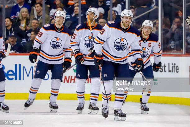 Leon Draisaitl of the Edmonton Oilers is all smiles as he leads teammates to the bench after a second period goal against the Winnipeg Jets at the...
